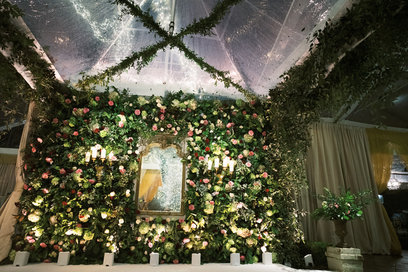 Wall of greenery and pink flowers at wedding reception
