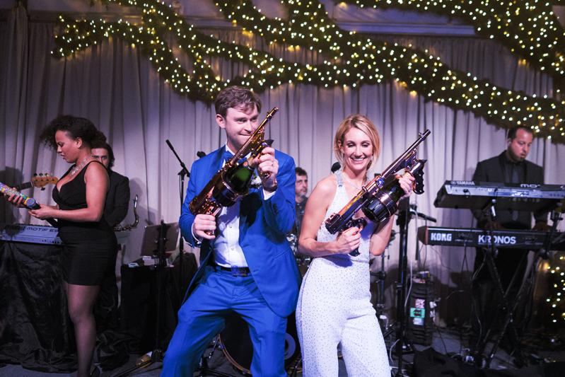 Bride and groom on stage with band during reception with confetti cannons.