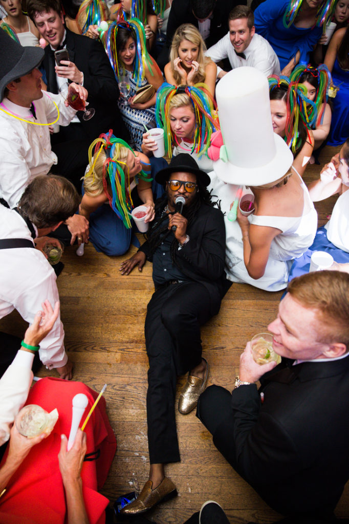 Punch lead singer surrounded by wedding guests on dance floor.