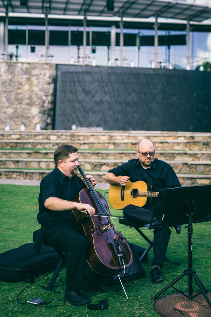 Cellist and guitarist duo playing during outside wedding ceremony