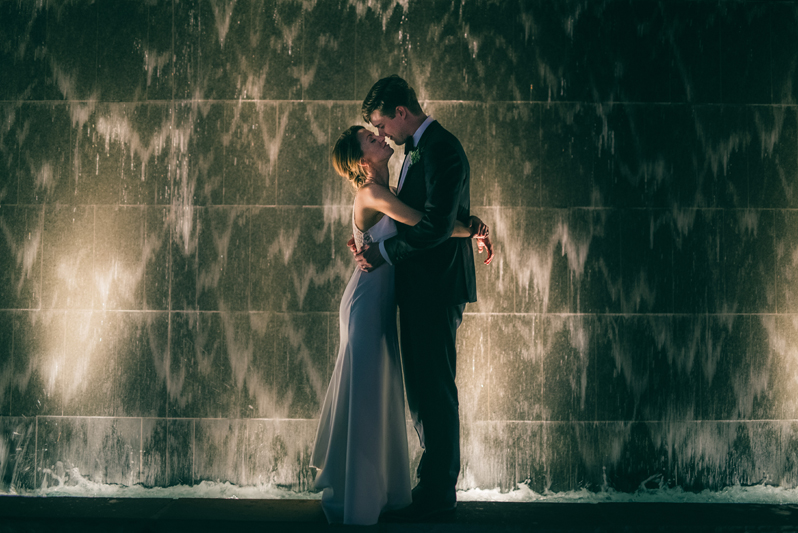 bride and groom in front of city waterfall