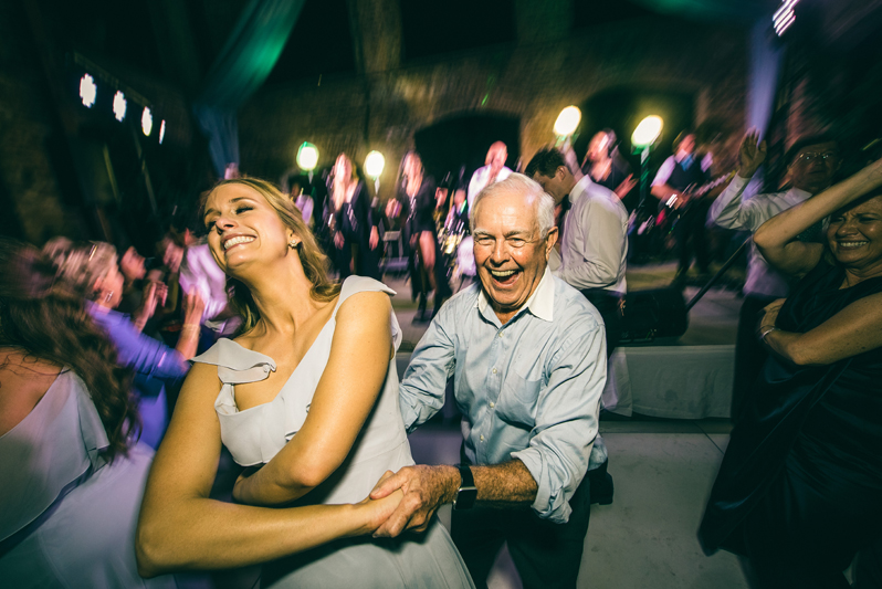 smiling couple dancing during wedding reception with wedding band in background