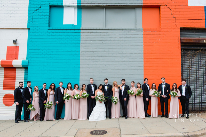 Bridal party in front of colorful wall
