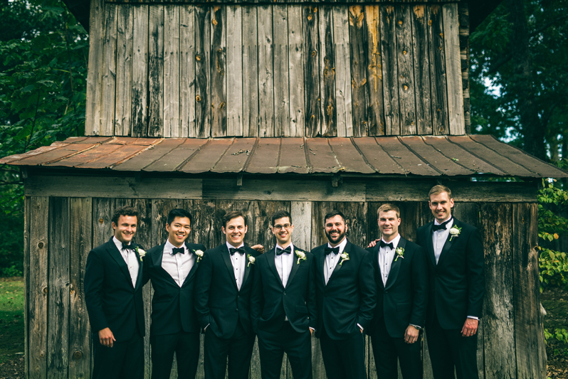 Groom and groomsmen in front of barn at Greensboro wedding.