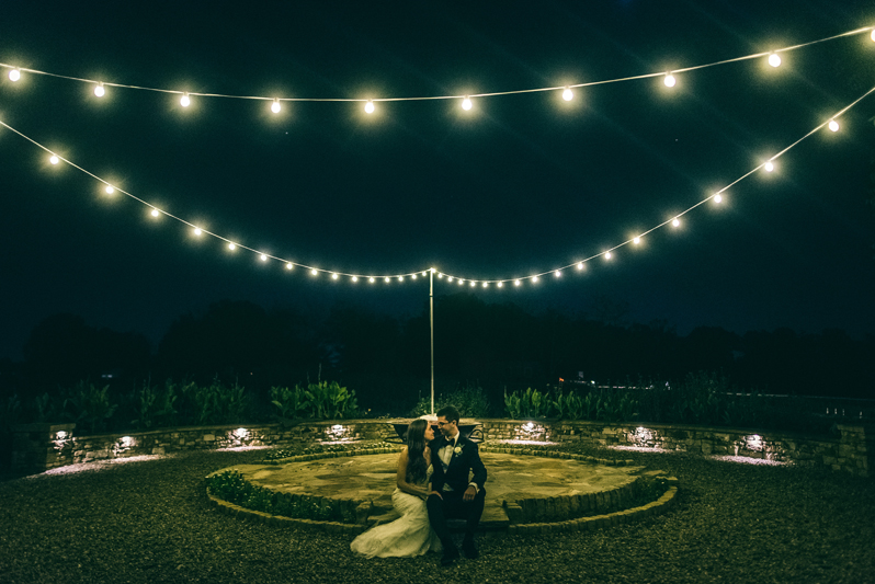 Bride and Groom kissing beneath string lights at Summerfield Farms wedding
