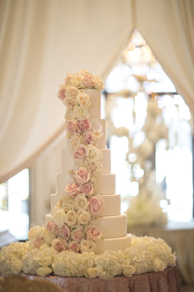 Six tier wedding cake with white and pink flowers