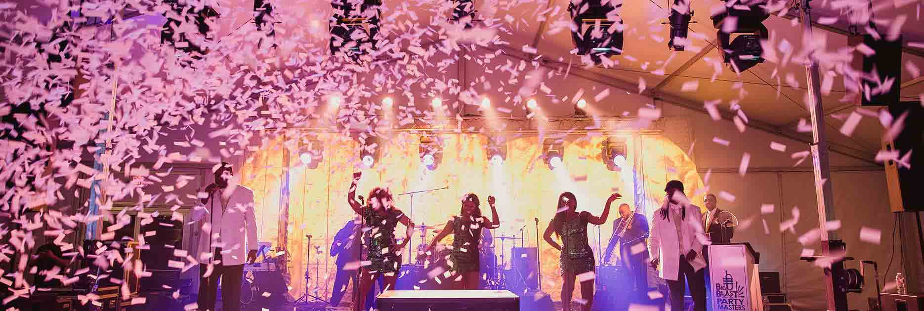 Live band performing on stage with falling confetti.